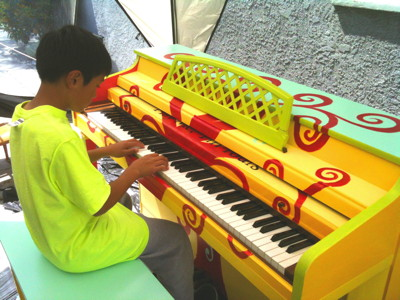 Julian Rachman plays a piano designed by his mother, Roseline Seng.