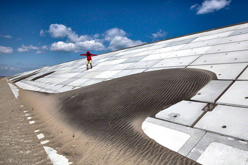 Image Caption: A woman makes her way down the seawall along the Kitakama and Ainokama coastline in Sendai, Japan. After the tsunami in 2011 the Japanese government has spent billions of yen on the reconstruction of a 31.8 km seawall along the Sendai coastline which is slated to be finished in 3 to 4 months. Commissioned photograph for the exhibition. ©Paula Bronstein.