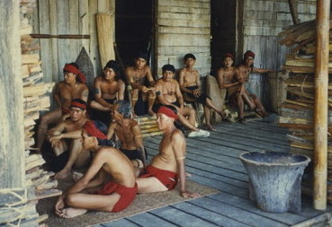 Borneo: tribespeople lounging and waiting.