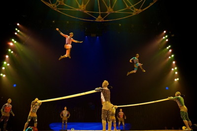 A gravity-defying team of ten acrobats bounces on flexible planks to execute leaps, somersaults and high tumbles while catapulting through the air.
