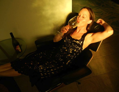 Carrie Graber sipping some of the LXV wine that bears her painting on its label. Self-portrait by the artist.