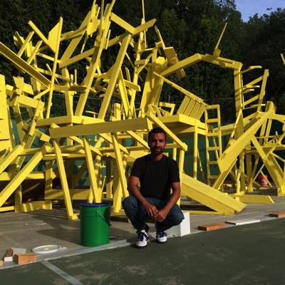 Artist Gustavo Godoy squatting with set -sculpture. Photo by Pauline Adamek.